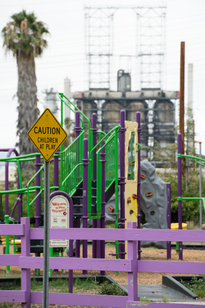 An oil refinery and highway are visible over the fence of a Long Beach child care center. KPCC reporters Deepa Fernandes and Sarah Monte investigate the effect of air pollution on early childhood development by taking air quality readings outside of child care centers located in Los Angeles County.
