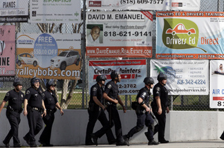 A group of police officers search outside El Camino Real High School in the Woodland Hills section of Los Angeles, Wednesday, Jan. 19, 2011.