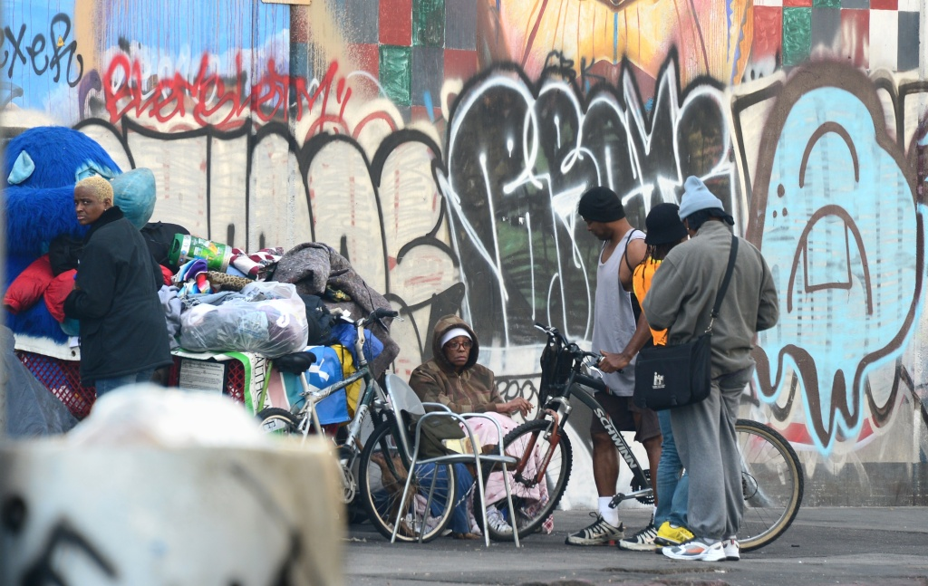 A homeless woman sits amid their belongings on a street in downtown Los Angeles, California, on January 8, 2014. Poverty in the world's largest economy remains far from being eradicated fifty years after President Lyndon Johnson declared a war on poverty in America in his first State of the Union address on this date in 1964, with a US Census Bureau report revealing on January 7 that nearly one in three Americans experienced poverty for at least two months during the global recession between 2009 and 2011. And in 2012, poverty affected some 47 million Americans, including 13 million children.