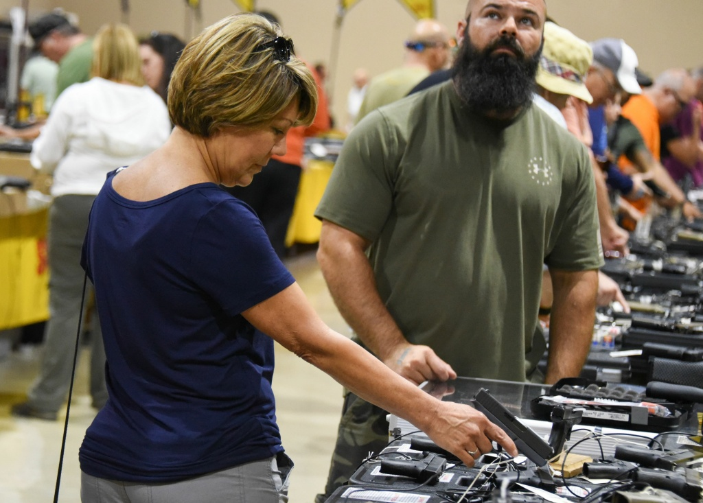 A gun enthusiast holds a weapon during the South Florida Gun Show at Dade County Youth Fairgrounds in Miami, Florida, on February 17, 2018.