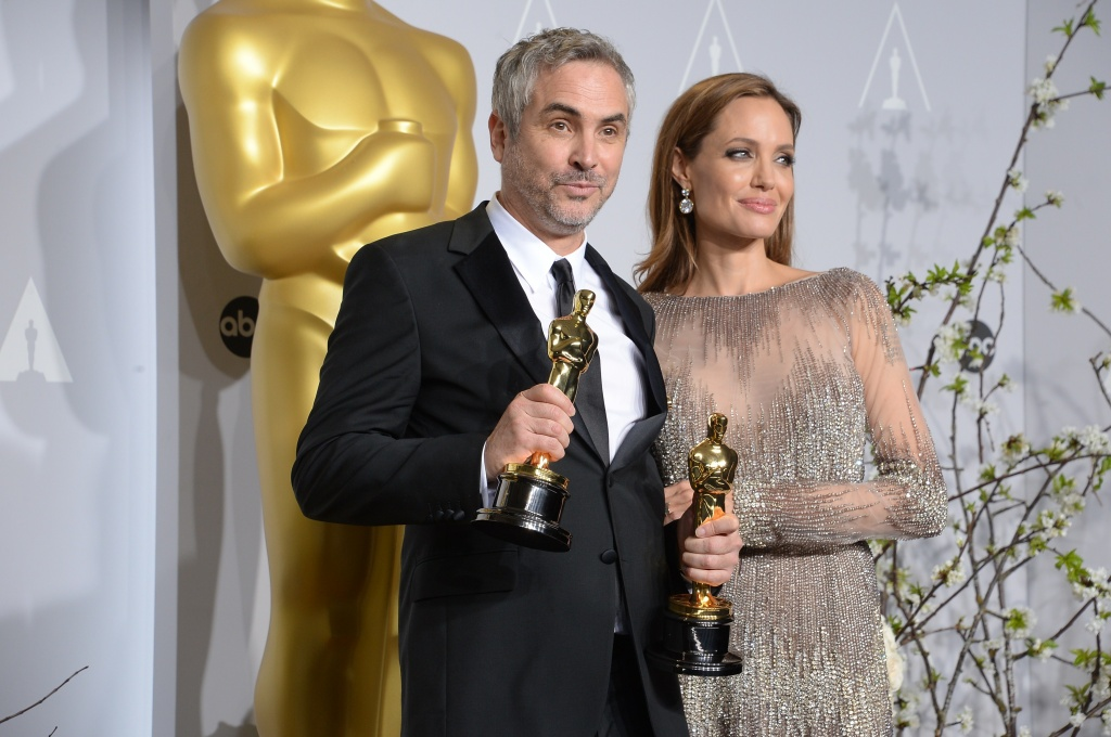Director Alfonso Cuarón (L), winner of Best Achievement in Directing for 'Gravity', and actress Angelina Jolie pose in the press room during the 86th Academy Awards on March 2nd, 2014 in Hollywood, California.