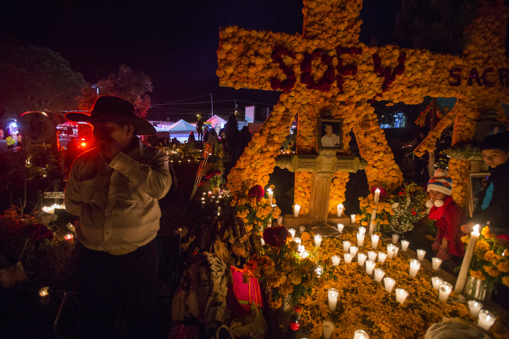 People attend to the graves of loved ones on the eve of the Day of the Dead at the cemetery of Tzintzuntzan in Patzcuaro, Michoacan, Mexico on November 1, 2016.