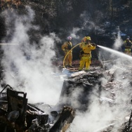 Firefighters work to contain embers on the remains of a house destroyed by the Clayton Fire in Lower Lake, California, August 15th, 2016. A 40-year old man has been arrested on suspicion of setting the fire.