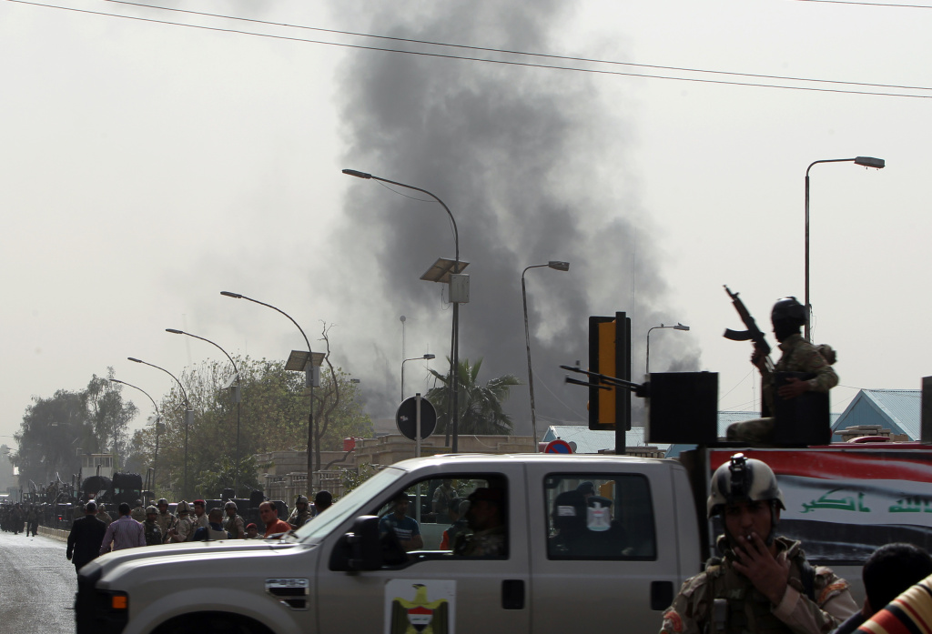 Smoke billows from the scene of a bomb attack in Baghdad, on March 14, 2013. A coordinated string of bombings and brazen assault on a ministry near Baghdad's heavily fortified Green Zone killed 18 people, in the Iraqi capital's deadliest violence this month.