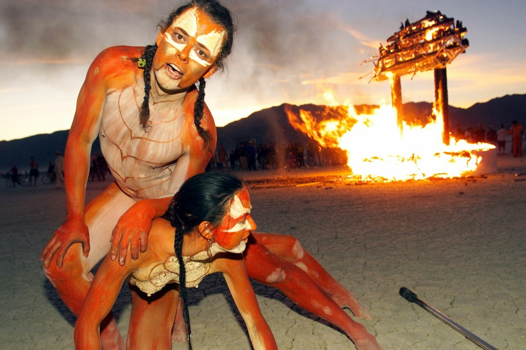 Thomas Wood and his companion, artists based in California, perform in front a wood structure set in fire at Black Rock City's Burning Man festival in Nevada on September 4, 1999.