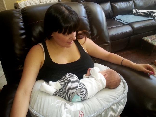 Baby Ivan Gomez, 12 weeks, naps on his mom Rochelle Gonzalez's lap after breastfeeding.