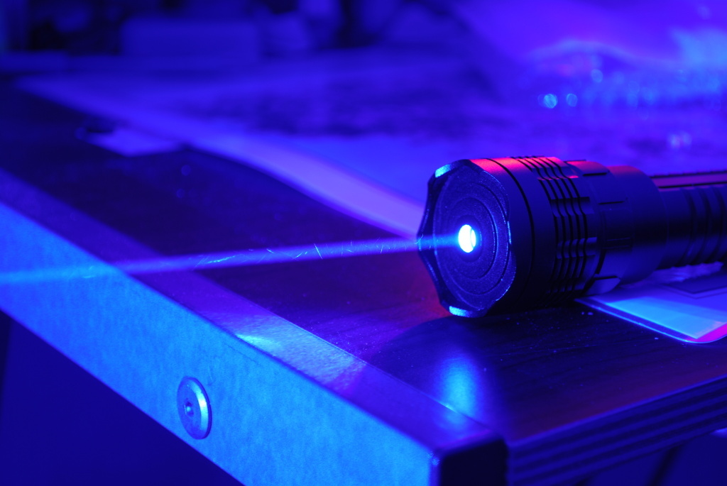 This Creative Commons photo shows a high-power blue laser with no lenses attached lasing in the dark. The FBI is offering a $10,000 dollar reward for information leading to the arrest of someone who points a laser beam at an aircraft.