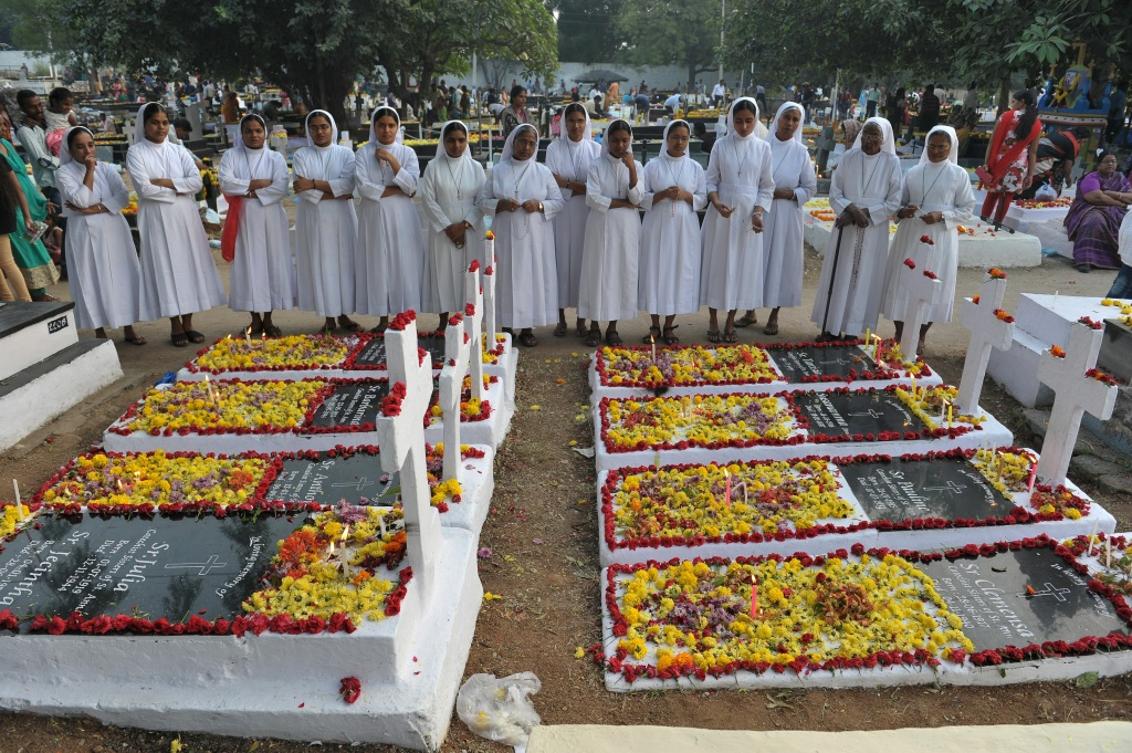 Indian Catholic nuns offer prayers at the graves of deceased sisters at a cemetery during All Souls Day in Hyderabad on November 2, 2016.