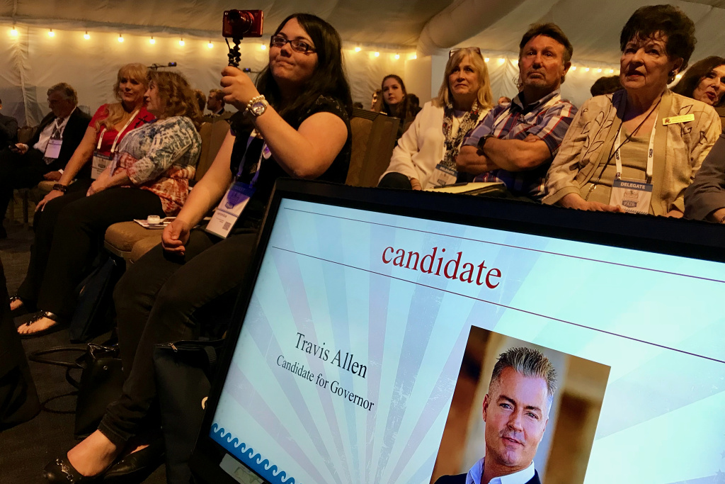 Attendees of the California Republican Party convention watch gubernatorial candidate Travis Allen on stage in San Diego.