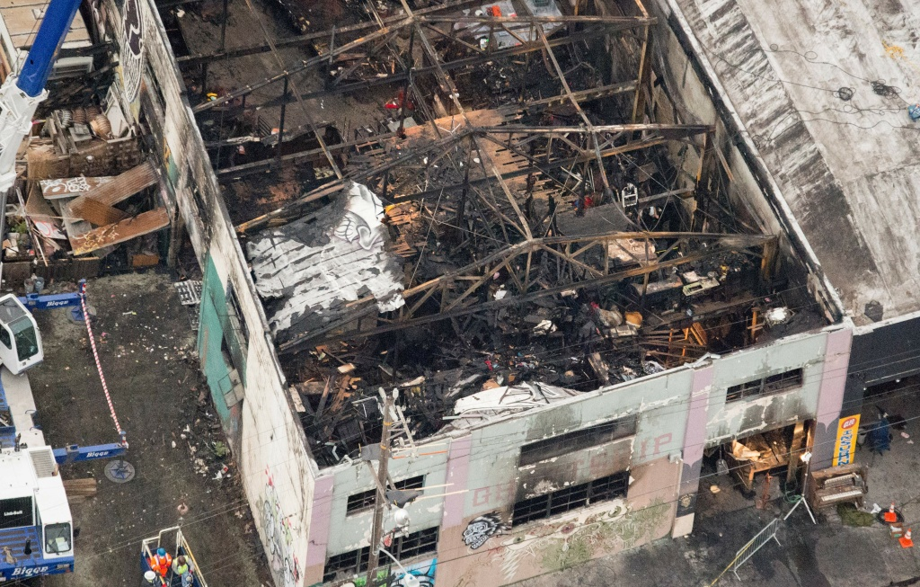 This aerial photo shows the remains of a fire ravaged warehouse on December 05, 2016 that killed at least 36 people in Oakland, California. The death toll from a massive weekend fire at a warehouse near San Francisco shot up to 36, as authorities launched a criminal probe and pushed forth with recovery efforts.
