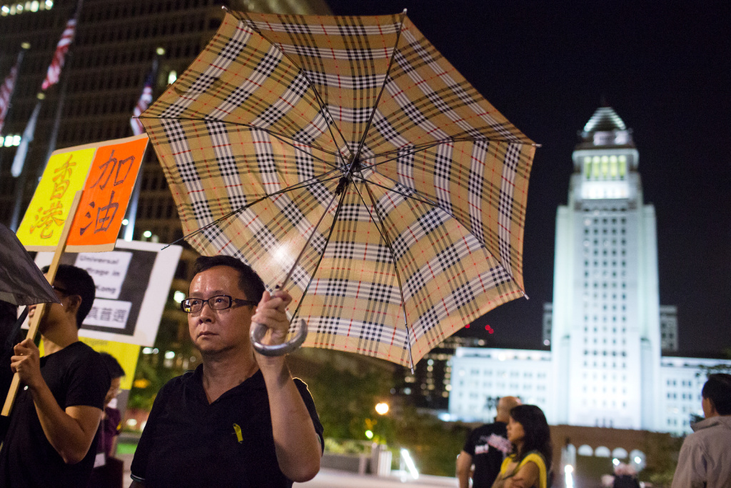 Attendees open umbrellas as a symbolic gesture during a vigil on Wednesday night, Oct. 1 at Grand Park in support of pro-democracy demonstrations happening in Hong Kong.