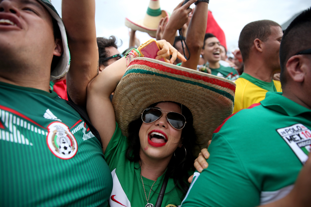 Mexican soccer team fans react to their team winning the match against Cameroon as they watch it on the giant screen showing the match at the FIFA World Cup Fan Fest on Copacabana beach on June 13, 2014 in Rio de Janeiro, Brazil.  Mexico won the game 1-0 during the second day of the World Cup tournament.