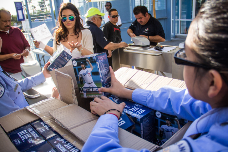 Los Angeles Police Department Cadets Joshua Villalta, left, and Ana Cortez, center, hand  out Clayton Kershaw bobbleheads during a giveaway at Dodger Stadium on Thursday, April  24, 2014.