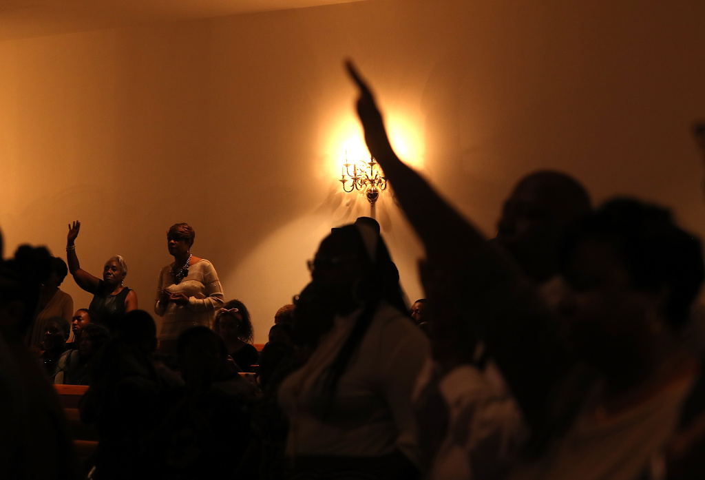 Parishioners look on as Democratic presidential nominee former Secretary of State Hillary Clinton speaks during church services at Mt. Airy Church of God in Christ on November 6, 2016 in Philadelphia, Pennsylvania.