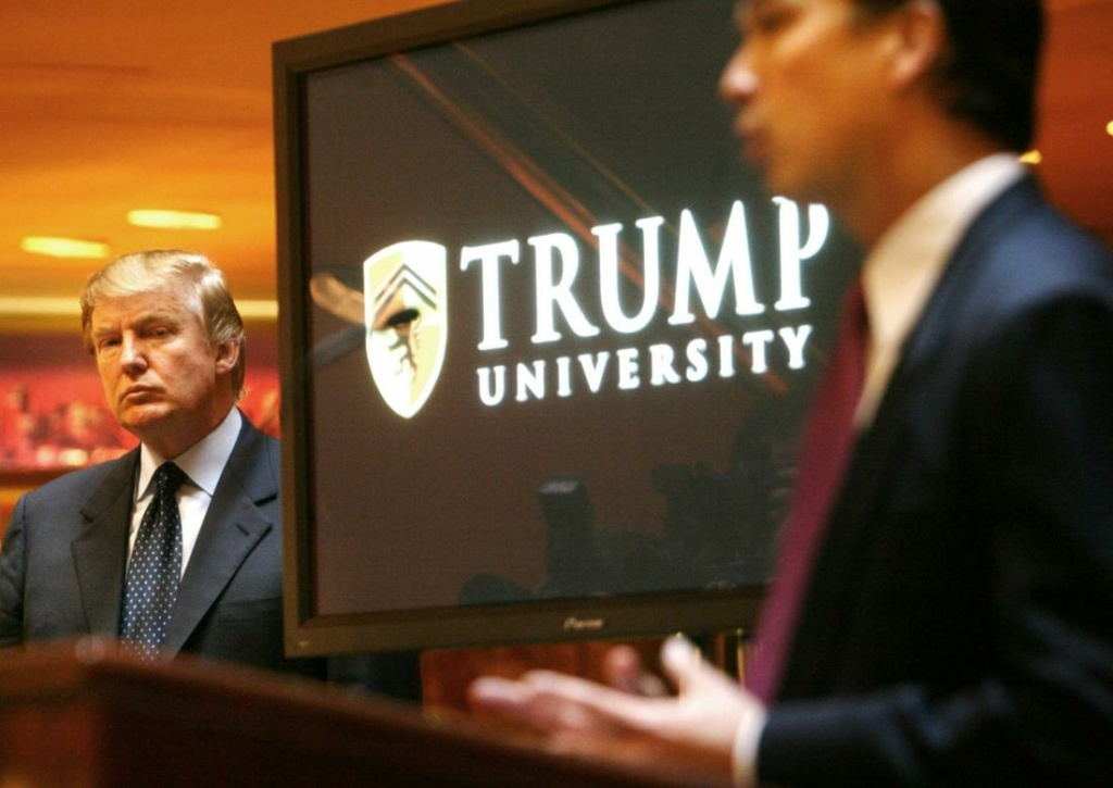 Donald Trump in front of his Trump University logo
