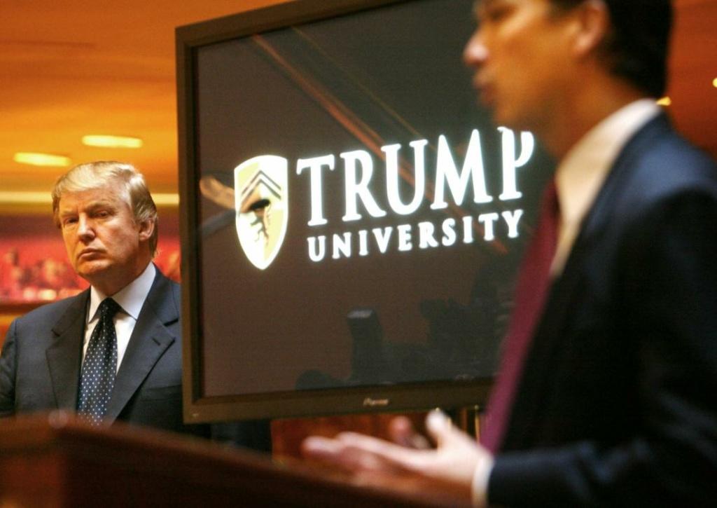 Donald Trump in front of his Trump University logo
