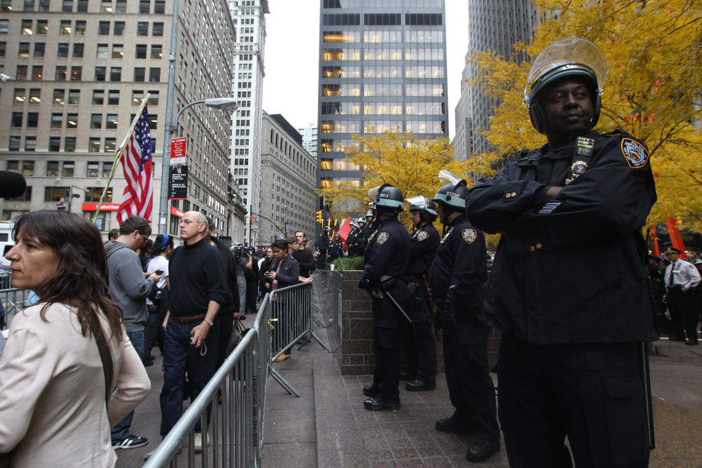 NEW YORK, NY - NOVEMBER 15:  Occupy Wall Street protesters and police stand outside Zuccotti Park after police removed the protesters from the park early in the morning on November 15, 2011 in New York City. Hundreds of protesters, who rallied against inequality in America, have slept in tents and under tarps since September 17 in Zuccotti Park, which has since become the epicenter of the global Occupy movement. The raid in New York City follows recent similar moves in Oakland, California, and Portland, Oregon.  (Photo by Mario Tama/Getty Images)