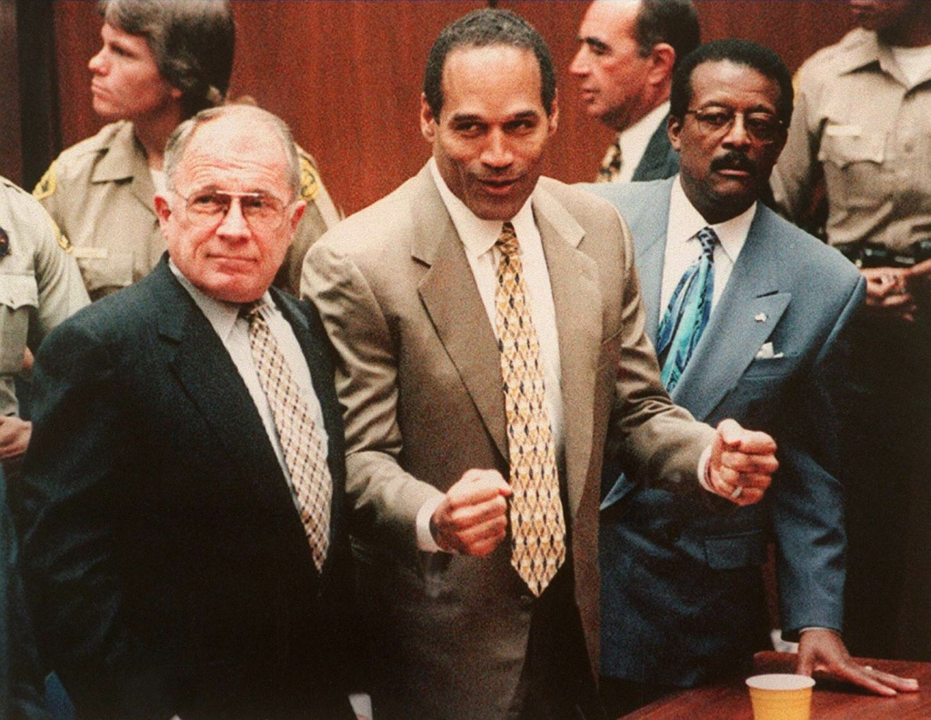 Defendant O.J. Simpson (C) cheers while standing with his attorneys F. Lee Bailey (L) and Johnnie Cochan Jr (R), after hearing the not guilty verdict in his criminal murder trial, Los Angeles, California on October 3, 1995.