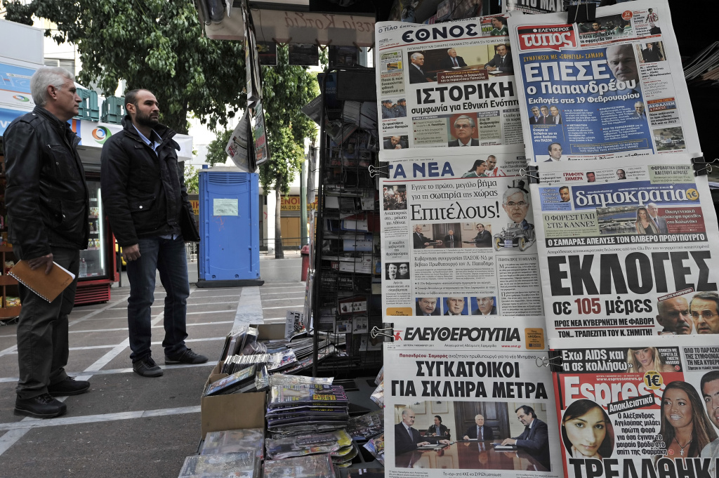 People stand next to a stand as newspaper bearing headlines on the greek crisis, are on display on November 7, 2011 in Athens. Greece's top politicians put the finishing touches to a unity government and begin talks on a new prime minister as markets react cautiously to a historic power-sharing deal to stave off bankruptcy and keep the country in the euro. AFP PHOTO / LOUISA GOULIAMAKI (Photo credit should read LOUISA GOULIAMAKI/AFP/Getty Images)
