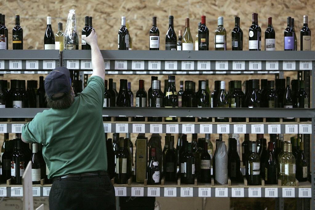 Wine.com worker Allen Bohnert stocks shelves with bottles of wine at the wine.com warehouse in Oakland, Califorina.