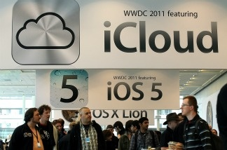 Attendees walk by signs for the new iCloud and iOS5 during the 2011 Apple World Wide Developers Conference.