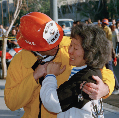 Hyun Sook Lee cries after being told by Dave Thompson of the Los Angeles City fire department that her 14-year-old son had been killed in the collapse of her apartment in the San Fernando Valley section of Los Angeles after an earthquake struck Southern California, Jan. 17, 1994. Her husband was also found dead. (AP Photo/Mark J. Terrill)