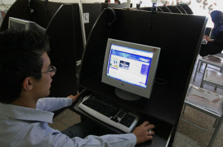 An Iranian youth browses a political blog at an internet cafe in the city of Hamadan.
