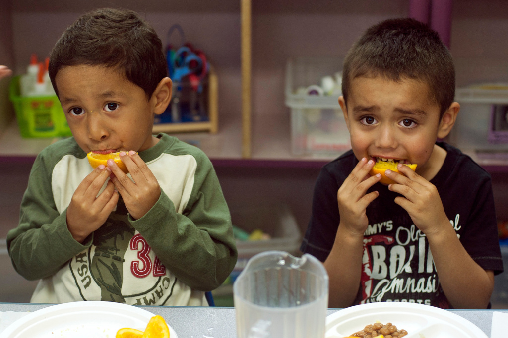 Samuel Rivera, left, and Daniel Sanchez finish their lunch with orange slices. If parents can't bring their child in the mornings, they will have to find another childcare for their kids.