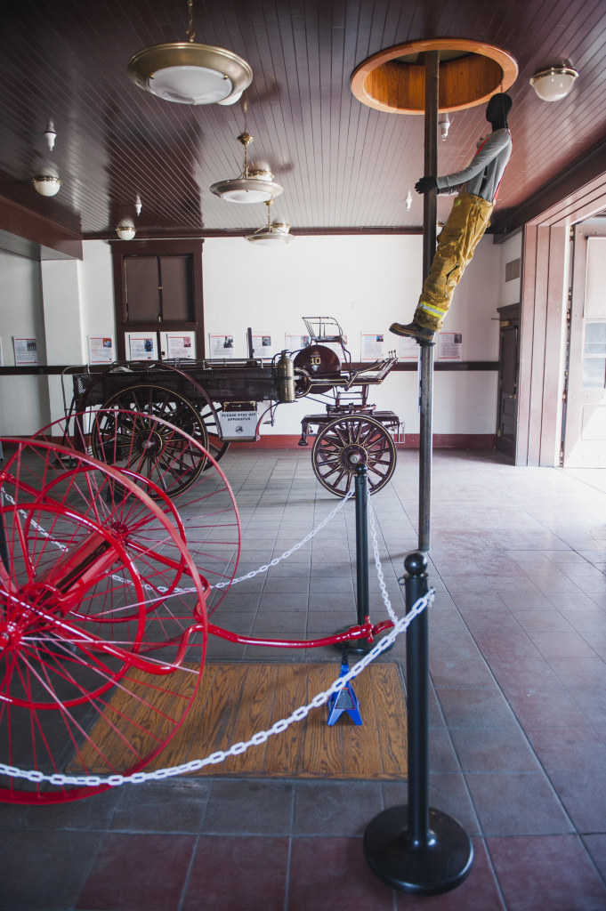 Antique fire carts and a mannequin descending a fire pole are on display on the first floor of the African American Firefighter Museum in Los Angeles, California.