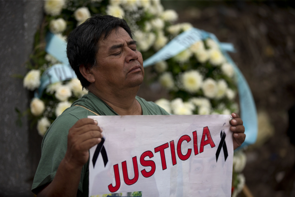 A man holds a banner that reads in Spanish