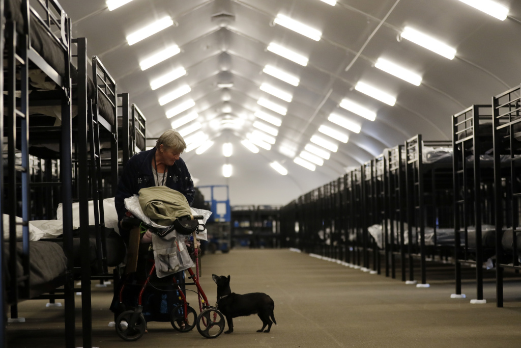 Verna Vasbinder prepares her her new bunk in the city's new Temporary Bridge Shelter for the homeless as her dog, Lucy Lui, looks on Friday, Dec. 1, 2017, in San Diego. The first of three shelters opened Friday, which will eventually provide beds for up to 700 people, as the city struggles to control a homeless crisis gripping the region.