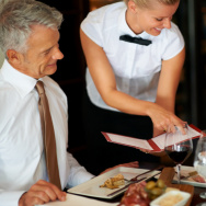 Young waitress shows the menu to mature couple