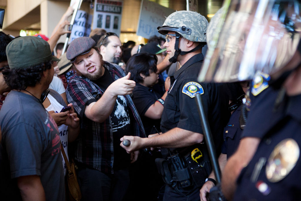 ANAHEIM, CA - JULY 24: Protesters clash with police at Anaheim City Hall to show their outrage for the shooting death of Manuel Angel Diaz, 25, on July 24, 2012 in Anaheim, California. Diaz was fatally shot July 21 by an Anaheim police officer and has sparked days of protests by the angered community. (Photo by Jonathan Gibby/Getty Images)