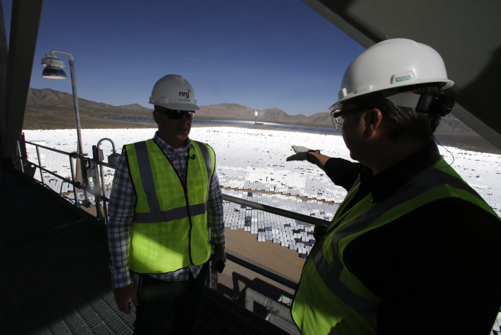 Jeff Holland, left, talks with Noel Hanson  near a boilers that sit on 459-foot towers Tuesday, Feb. 11, 2014 in Primm, Nev. The Ivanpah Solar Electric Generating System, sprawling across roughly 5 square miles of federal land near the California-Nevada border, was scheduled to open formally Thursday after years of regulatory and legal tangles.