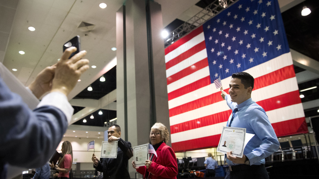 FILE: Immigrants pose with U.S citizenship certificates in front of a large U.S. flag after a naturalization ceremony at the Los Angeles Convention Center.
