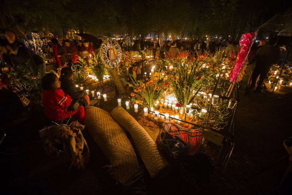 A woman attends to the grave of a loved one on the eve of the Day of the Dead at the cemetery of Tzintzuntzan in Patzcuaro, Michoacan, Mexico on November 1, 2016.