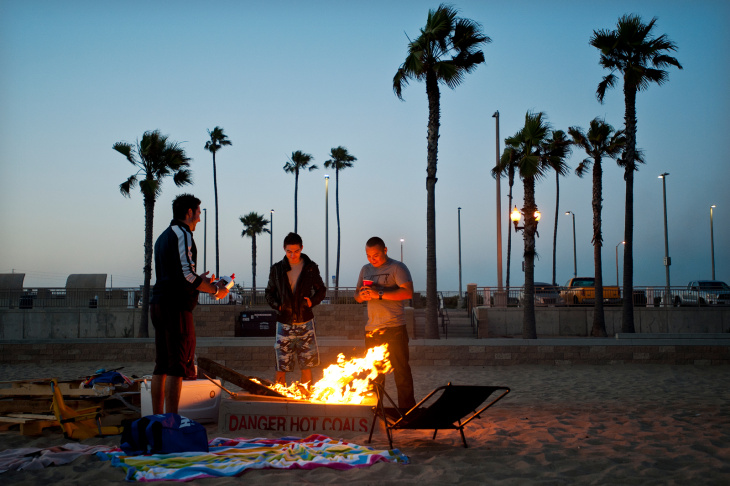 Jerry Wymore, Paige Brown, Sabrina Fuentes, and Nick Kern of Apple Valley roast marshmallows on Thursday evening, June 6, at a fire pit on Huntington Beach.