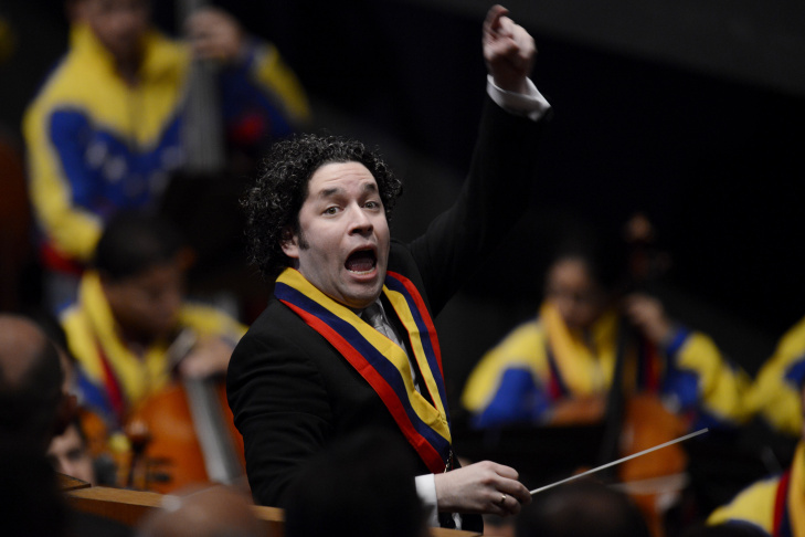 Venezuelan conductor and director of Los Angeles's Philharmonic Orchestra Gustavo Dudamel (R and on screen L) gestures with his musicians of the Youth Symphonic Orchestra during a free concert in the center of Caracas on July 26, 2009. To celebrate the 442nd anniversary of the city of Caracas, which usually has no street cultural events due to urban violence, free classical concerts were organized in the streets.