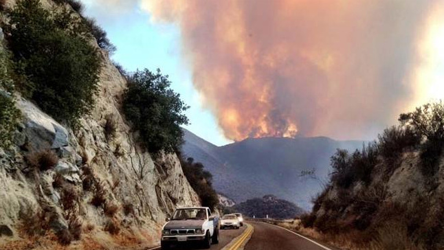 Flames from the Falls Fire in Riverside rise above a mountain on Aug. 5, 2013.