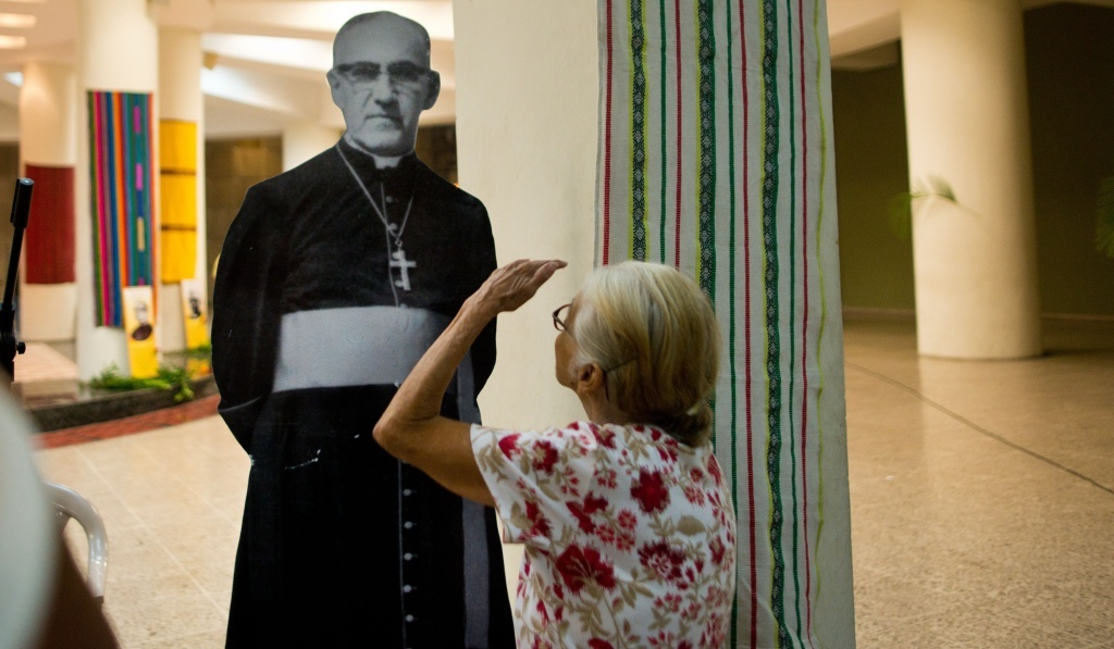 A Catholic faithful looks at a portrait of Monsignor Oscar Arnulfo Romero at his grave in the cathedral of San Salvador on March 24, 2014, during the commemoration of the 34th anniversary of his murder. The Pope Francis formally declared Romero a martyr Tuesday.