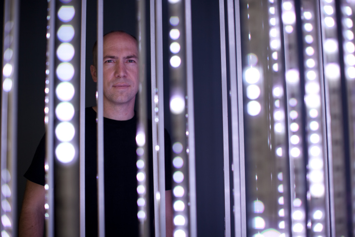 Dan Goods, visual strategist at the Jet Propulsion Laboratory creates projects that visualize NASA missions. He is framed by The Pulse, a data visualization installation that reacts when information is sent to and received by spacecraft in deep space.