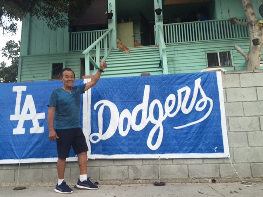 70-year-old Joseph Martinez has lived near Chavez Ravine all his life. He displays a hand-made Dodgers sign during Game 1 of the 2017 World Series.