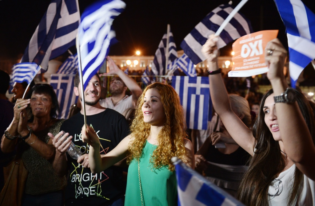 People celebrate in Athens on July 5, 2015 after the first exit-polls of the Greek referendum. Over 60 percent of Greeks rejected further austerity dictated by the country's EU-IMF creditors in a referendum, results from 20 percent of polling stations showed.