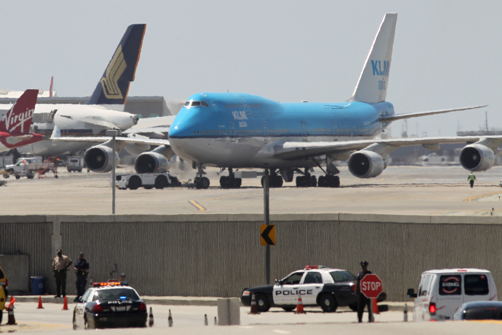 File: Police officers check vehicles at a traffic security check point as jets taxi into take-off position at Los Angeles International Airport (LAX) on April 22, 2013.