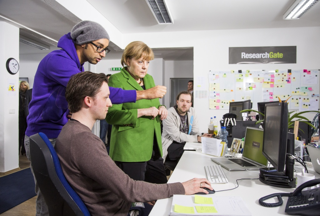 German Chancellor listens to manager Ijad Madisch (C) during her visit of the company Research Gate on in Berlin.