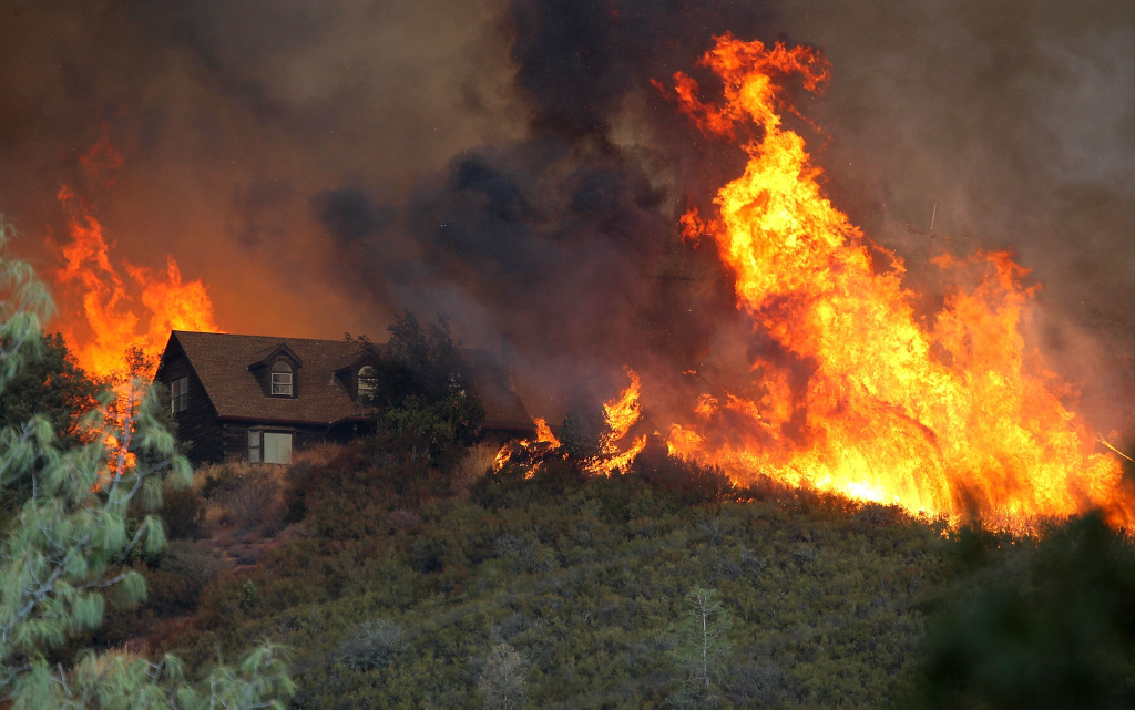 Flames from the Rocky Fire approach a house in Lower Lake, Calif., Friday.