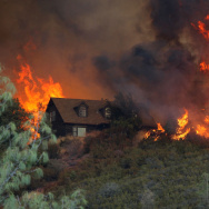 Flames from the Rocky Fire approach a house in Lower Lake, Calif., Friday. More than 5,000 firefighters are now battling large blazes in California; hundreds of residents are under evacuation orders in affected areas.