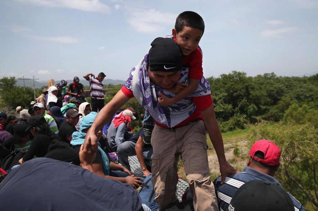 Central American immigrants arrive on top of a freight train for a stop on August 6, 2013 in Ixtepec, Mexico.