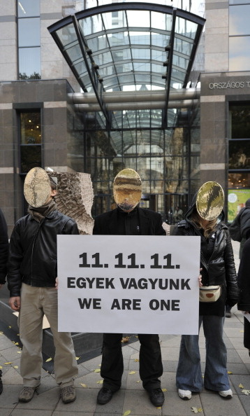 Hungarian and foreign activists and sympathizers of the 'True Democracy Now' group stand with a banner reading '11.11.11. We are one' in front of a bank in downtown Budapest on November 11, 2011