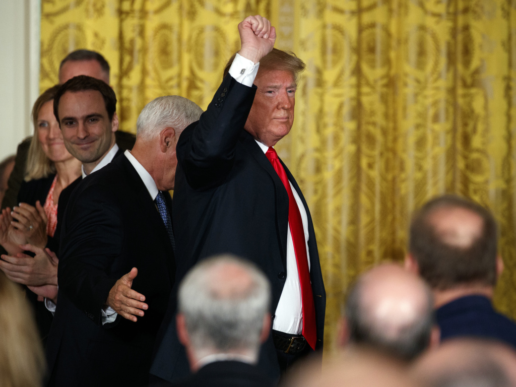 President Donald Trump pumps his fist as he leaves a meeting Monday in the East Room of the White House in Washington.